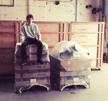 brewer sits on pallet of bottles