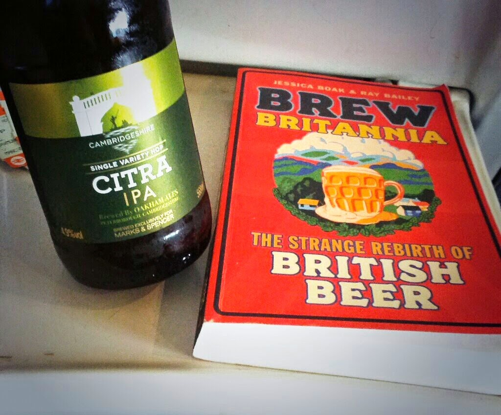 A bottle of Marks and Spencers Oakham Citra IPA, next to a copy of Boak and Bailey's Brew Britannia